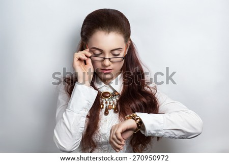 Studio shot of beautiful businesswoman, looking over her glasses on a wristwatch. Serious woman in white official blouse with watch on her hand, brown necklace. Hair dress curly brunette. Professional - stock photo
