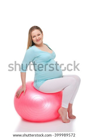 Studio shot of beautiful pregnant woman on white background. Woman exercising with fitness ball - stock photo