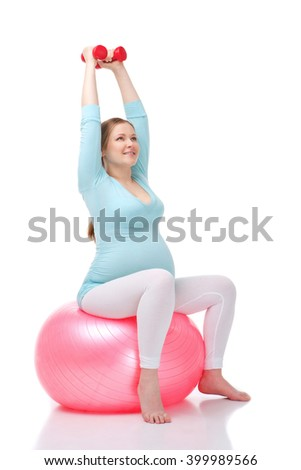 Studio shot of beautiful pregnant woman on white background. Woman exercising with fitness ball and dumbbells - stock photo