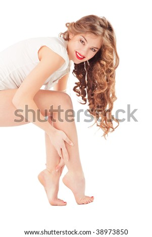 Studio shot of beautiful sexy woman showing her legs and long curly hair - stock photo
