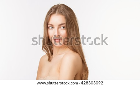 Studio shot of beautiful shirtless lady demonstrating her shoulders for photographer. Pretty woman looking sideway over white background.
