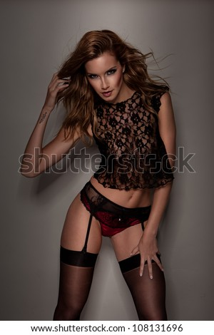 Studio shot of beautiful woman in stockings and sexy underwear on grey background - stock photo