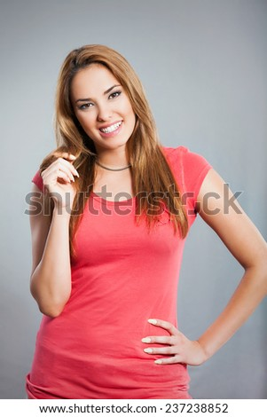 Studio shot of beautiful young woman posing against gray background