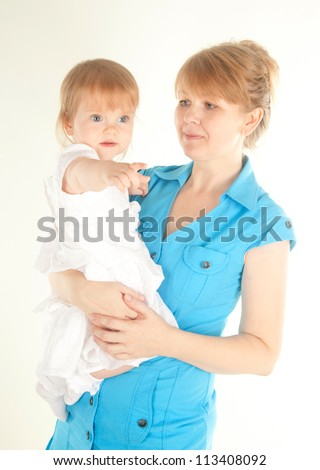 studio  shot of blond mother embracing her little daughter