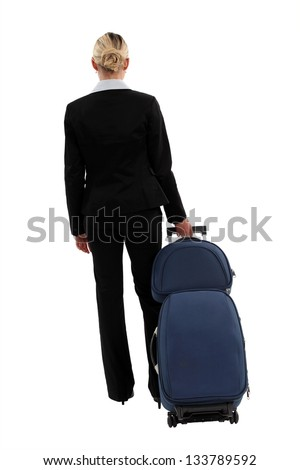studio shot of businesswoman pulling luggage - stock photo
