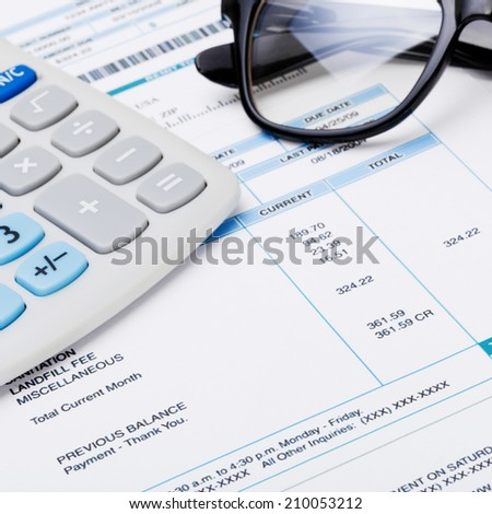 Studio shot of calculator and glasses over some receipt - stock photo