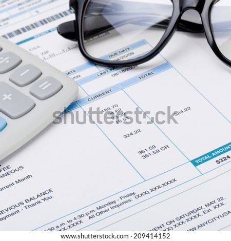 Studio shot of calculator and glasses over some receipt - 1 to 1 ratio - stock photo