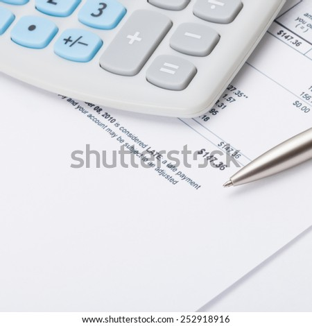 Studio shot of calculator and pen over some receipt under it - stock photo