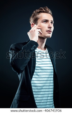 Studio shot of caucasian young businessman. Businessman using mobile phone - stock photo