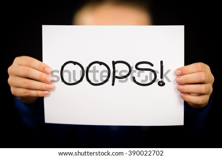 Studio shot of child holding a OOPS sign made of white paper with handwriting. - stock photo