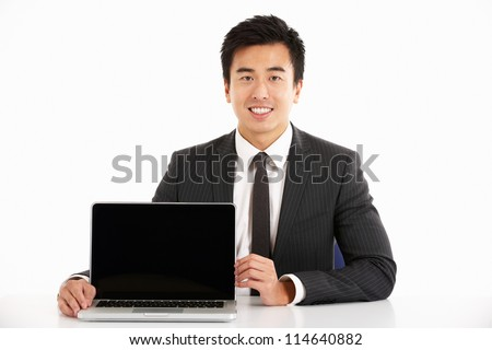 Studio Shot Of Chinese Businessman Working On Laptop
