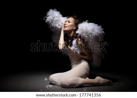 Studio shot of crying lovely girl dressed as angel