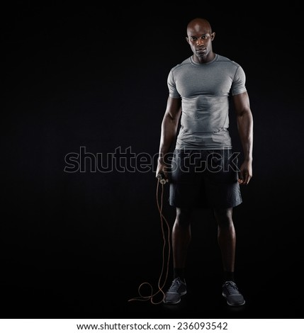 Studio shot of fit and muscular man with jumping rope standing on black background. Afro american male model with copyspace. Sports and fitness concept. - stock photo