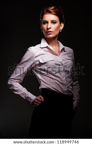 studio shot of graceful young female over dark background - stock photo