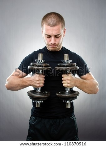 Studio shot of handsome sportsman with dumbbells on gray background - stock photo