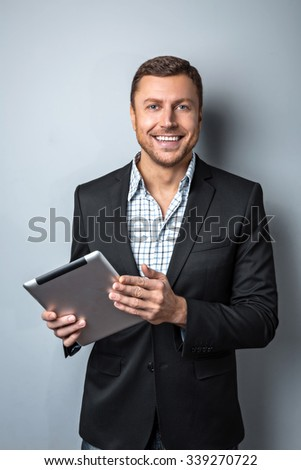 Studio shot of handsome young businessman on grey background. Man wearing jacket and shirt. Man smiling and holding tablet computer - stock photo