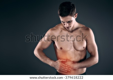 Studio shot of handsome young man with naked torso. Man suffering from abdominal pain. Red spot on belly