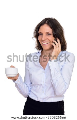 Studio shot of happy Caucasian woman talking on mobile phone while holding coffee cup isolated against white background