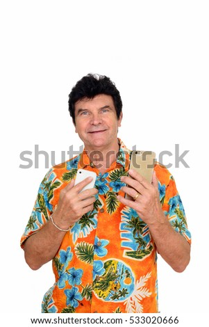 Studio shot of happy mature Caucasian man wearing Hawaiian shirt holding two mobile phones