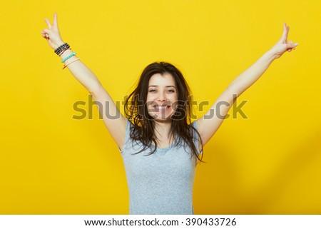 Studio shot of happy woman keeping hands raised over yellow wall - stock photo