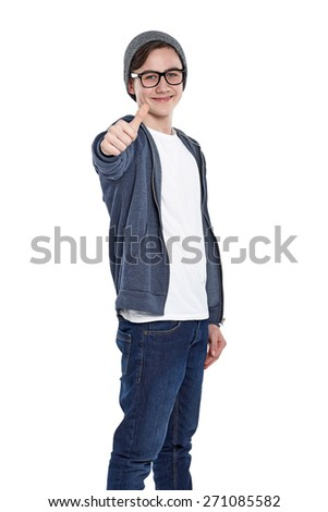 Studio shot of happy young boy gesturing thumbs up while standing over white background - stock photo