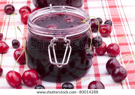 studio-shot of homemade cherry jam in a glass jar. - stock photo