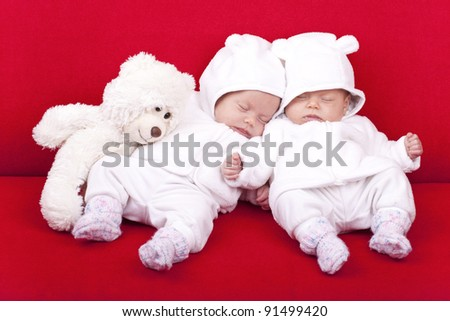 studio-shot of identical ( similar ) twin baby sisters resting and sleeping on a red sofa. - stock photo