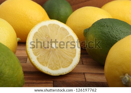 Studio shot of lemons and limes on wooden pad - stock photo