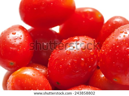 studio shot of little fresh plum tomatoes with water drops - stock photo
