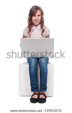 studio shot of little smiley girl with laptop. isolated on white background - stock photo