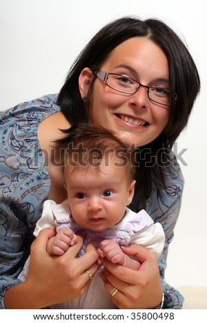 Studio shot of loving mother holding baby - stock photo