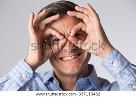 Studio Shot Of Man Making Spectacle Shape With His Hands - stock photo