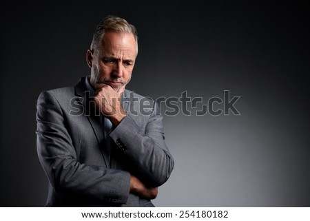 Studio shot of mature businessman looking down thinking over grey background  - stock photo