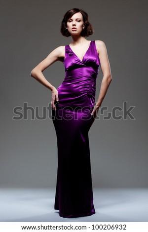 studio shot of model in beautiful dress over dark background - stock photo