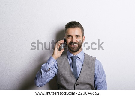 Studio shot of modern hipster businessman making a phone call with mobile phone - stock photo