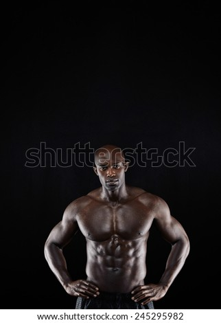 Studio shot of muscular man posing with his hands on hips against black background. Shirtless male african model with muscular build. - stock photo