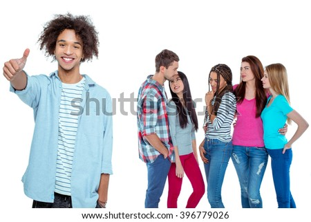 Studio shot of nice young multicultural friends. Beautiful people chatting. Focus on african boy. He looking at camera, showing thumb up and smiling. Isolated background - stock photo