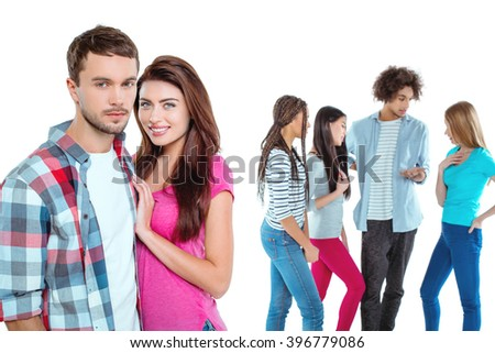 Studio shot of nice young multicultural friends. Beautiful people chatting. Focus on young couple. Couple looking at camera and smiling. Isolated background - stock photo