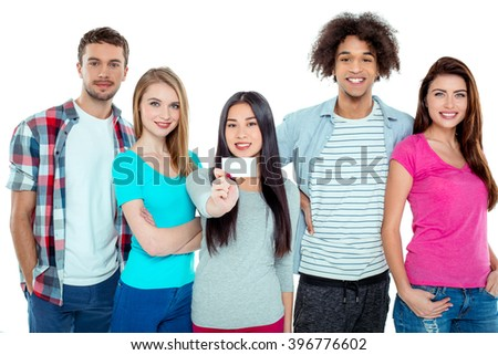 Studio shot of nice young multicultural friends. Beautiful people looking at camera and smiling. One girl in the middle holding empty visit card. Isolated background - stock photo