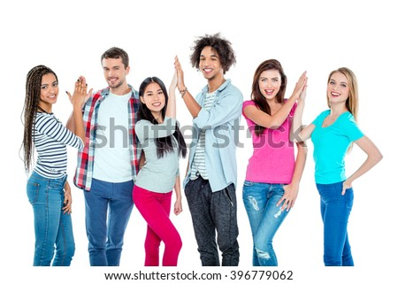 Studio shot of nice young multicultural friends. Beautiful people making high fives, looking at camera and cheerfully smiling. Isolated background