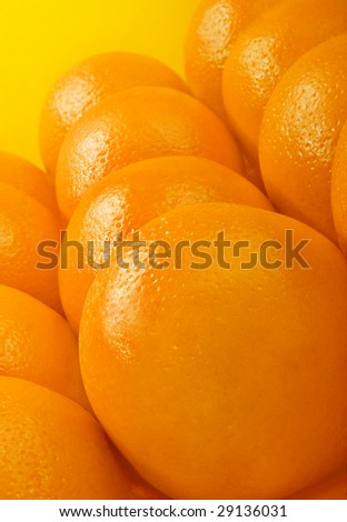 Studio shot of oranges over yellow background