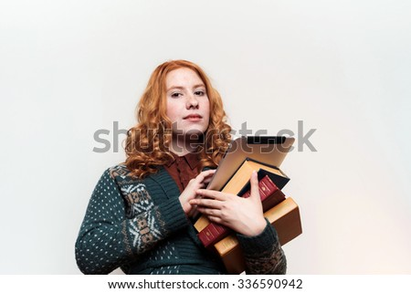 studio shot of redhead girl with books and tablet. Education concept