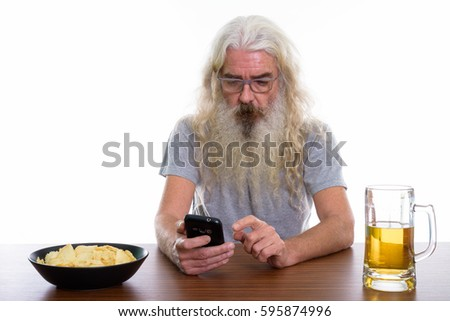 Studio shot of senior bearded man using mobile phone with bowl of potato chips and glass of beer on wooden table