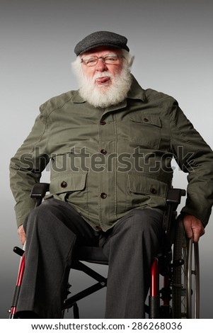 Studio shot of senior man sitting on wheel chair teasing, sticking out his tongue against grey background - stock photo