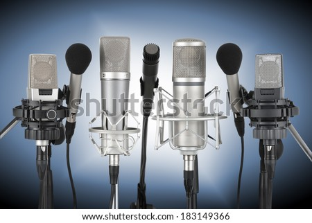 Studio shot of seven professional microphones in a row on blue background with spotlight - stock photo