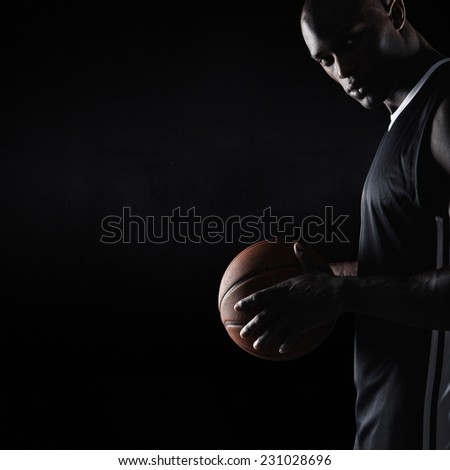 Studio shot of strong young man holding basketball looking at camera with copyspace. African basketball player. - stock photo