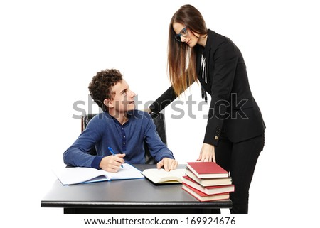 Studio shot of teacher standing next to the student's desk  talking, isolated over white background - stock photo