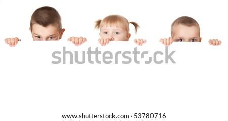 studio shot of three child behind white board - stock photo