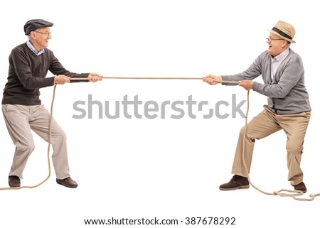 Studio shot of two cheerful seniors competing in a tug of war isolated on white background - stock photo