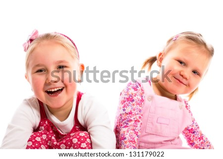 studio shot of two laughing sisters